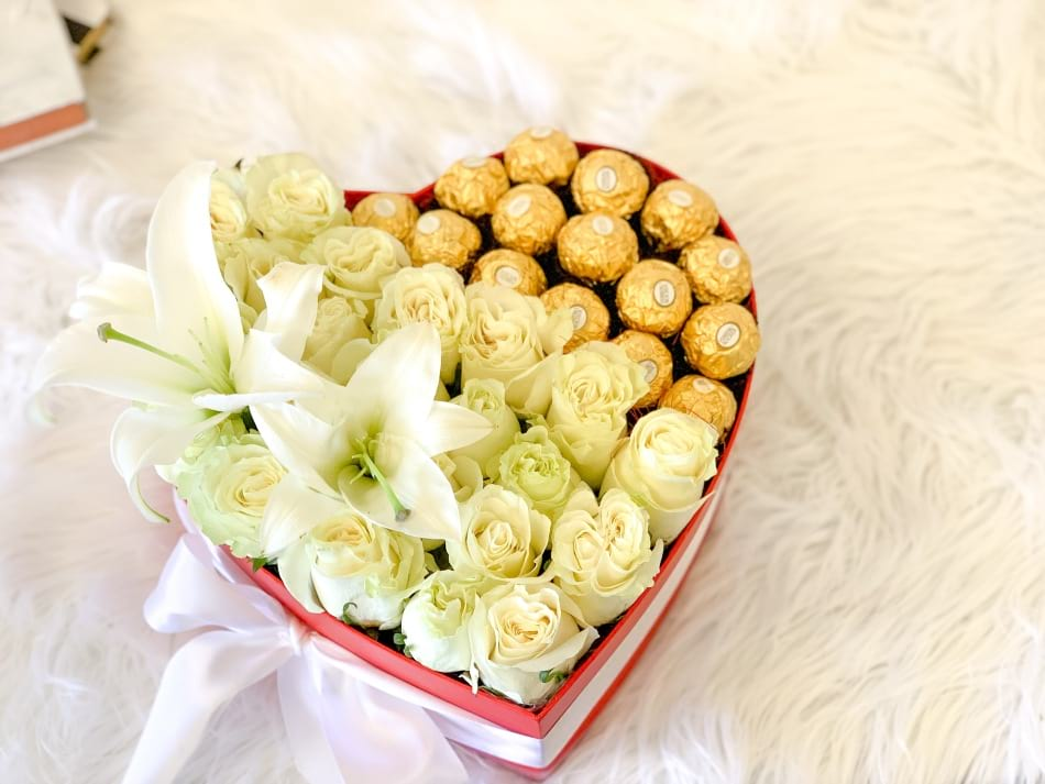 Gift heart box with white roses lilies and chocolates